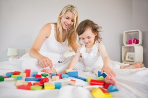 View of mother and daughter playing with building blocks on bed at home